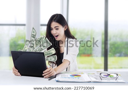 The woman in front of the laptop with fly out dollars - stock photo