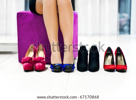 The woman in shop chooses shoes - stock photo