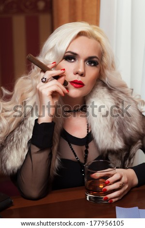 The woman in strict clothes in a retro style the tritsatykh of years. The mafia, plays poker, smokes a cigar or cigarettes and drinks whisky. - stock photo