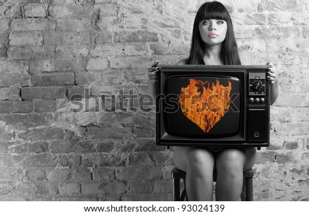 The woman in the image of the devil keeps an old television with the image of a fiery heart on the screen. - stock photo