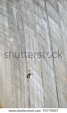The woman is bungee jumping along the concrete wall. The Contra Dam is a popular bungee jumping venue in the Swiss Alps. - stock photo