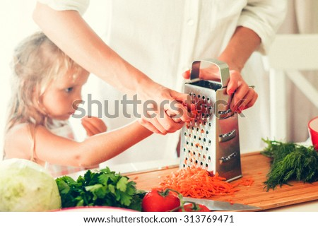 The woman is cooking at the kitchen with daughter ( grating carrots ) - stock photo