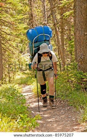 The woman is hiking up the Lake Otakomi trail in Glacier National Park - stock photo