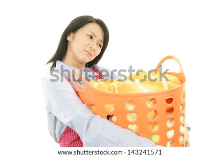 The woman is holding a Laundry basket - stock photo