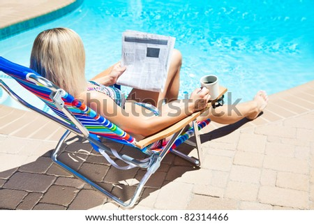 The woman is holding cup of coffee and reading newspaper by the pool - stock photo