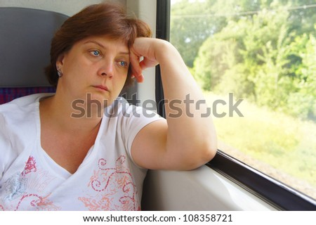 The woman is looking into window of train - stock photo