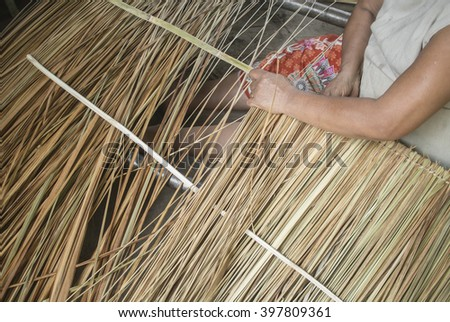 The woman is make roof from dry grass