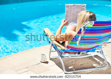 The woman is reading newspaper by the pool - stock photo