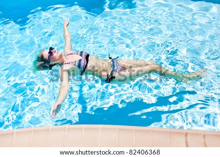 The woman is swimming in the pool - stock photo