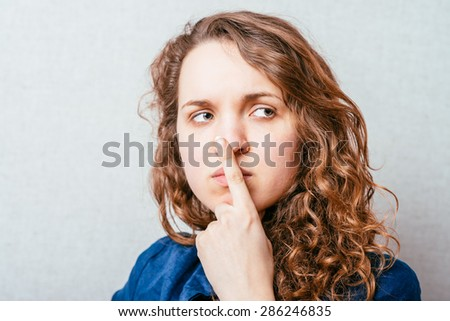 The woman is thinking, index finger on his nose. Gray background - stock photo