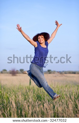 The  woman jumps in a grass - stock photo