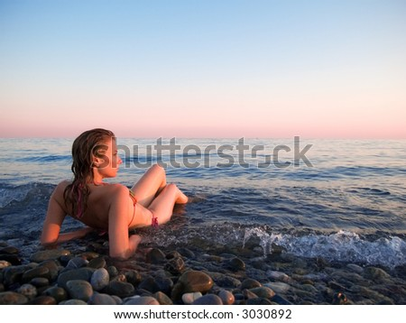 The woman lays in coastal waves