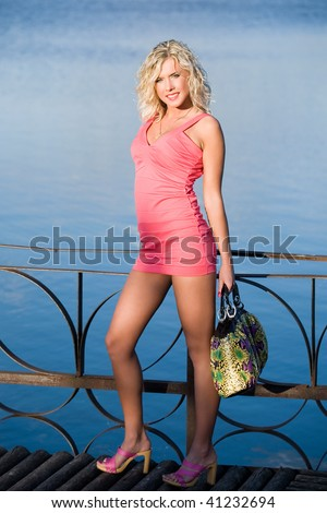 The woman leans against a handrail. - stock photo