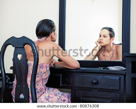 the woman looks in the mirror in vintage interior - stock photo