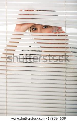The woman looks through jalousie - stock photo