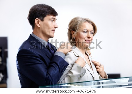The woman measures a jeweller necklace in shop - stock photo