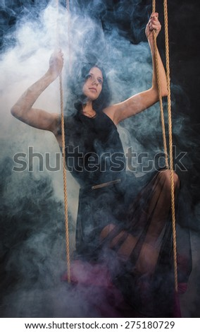 The woman on a swing in a smoke  - stock photo