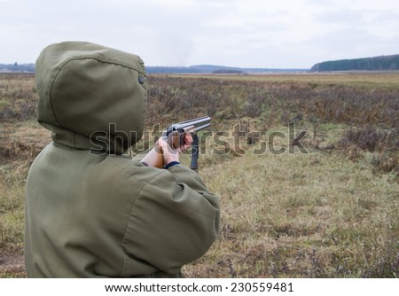The woman on hunting shooting rifle - stock photo