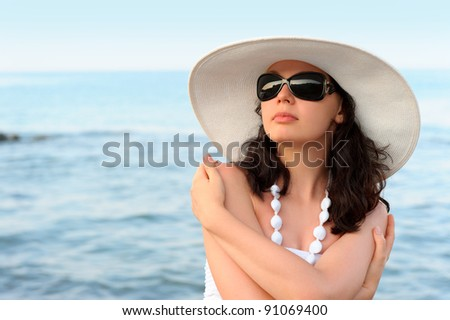 The woman on seacoast. In sun glasses, a sundress, a hat. - stock photo