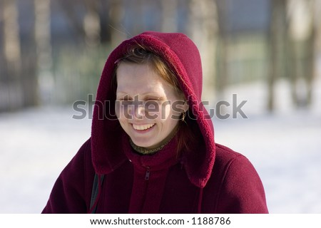 The woman on walk in solar winter day. Is pleased and smiles. - stock photo