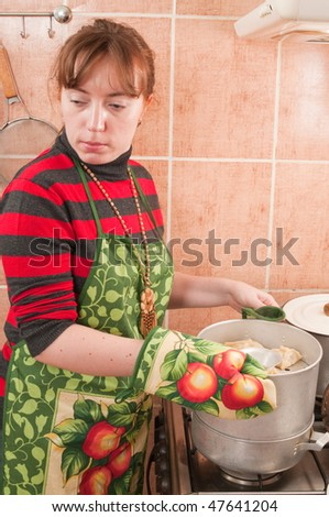 The woman, pans and the gas furnace. - stock photo