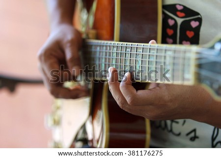 The woman plays an acoustic guitar closeup