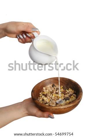 The woman pours milk in porridge.  Isolated on white background. - stock photo