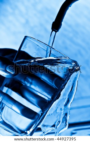 The woman pours water from the crane in a glass - stock photo