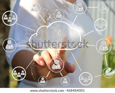 The woman presses on the cloud icon with the technology of fingerprints on the touch screen. Security of data storage .The use of new technologies and business outside the city.Web icons.