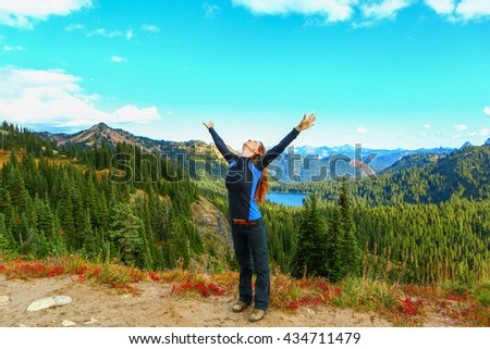 The woman raised her hands up, happy. Mount Rainier national park, Washington - stock photo