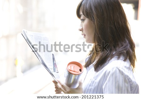 The woman reading a newspaper at the station - stock photo
