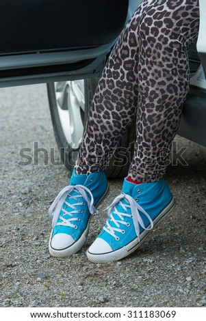 The woman rising out of the car with blue sneakers in Finland. She is wearing a leopard-print pants.