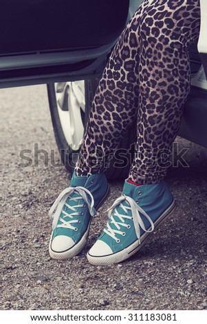 The woman rising out of the car with blue sneakers in Finland. She is wearing a leopard-print pants. Image includes a effect.