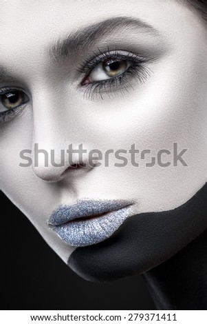 The woman's face with black and white make-up and glitter on her lips close-up