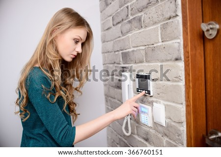 The woman set's the desired temperature in home heating system - stock photo