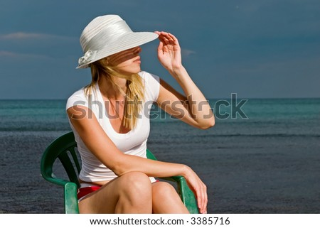 The woman sits on a sea background - stock photo