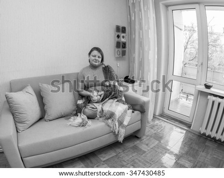 The woman sits on a sofa in the room