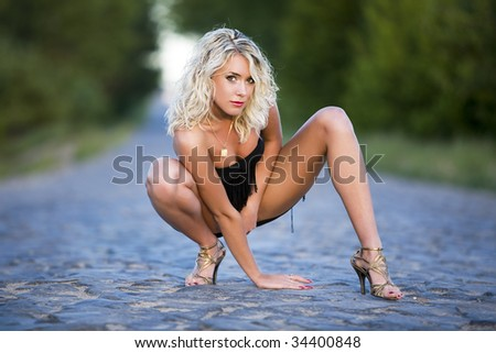 The woman squats on paved road. - stock photo