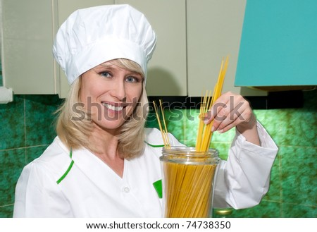 The woman the cook from a spaghetti on kitchen - stock photo