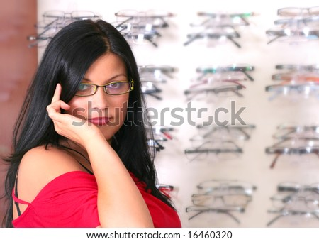 the woman tries glasses - stock photo