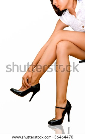 The woman unbuttons patent-leather shoes - stock photo