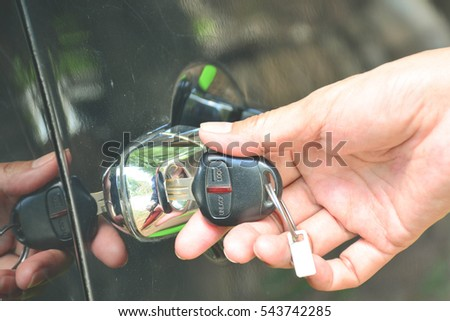 The woman uses the key to open the car.
