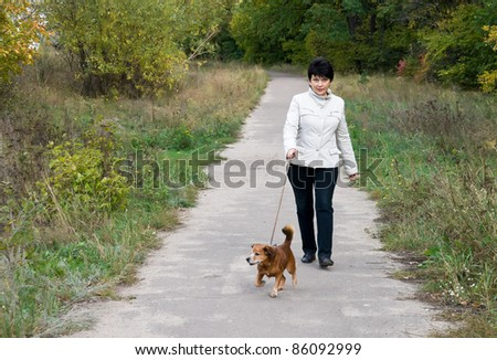 The woman walks with dog in autumn park - stock photo
