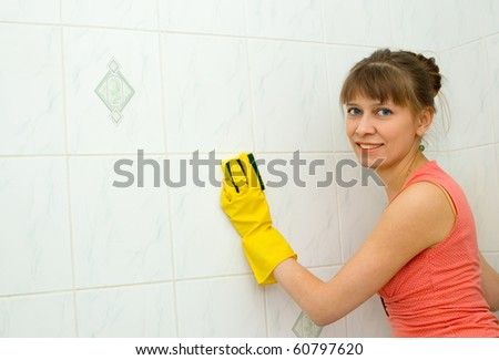 The woman washes a tile in a bathroom