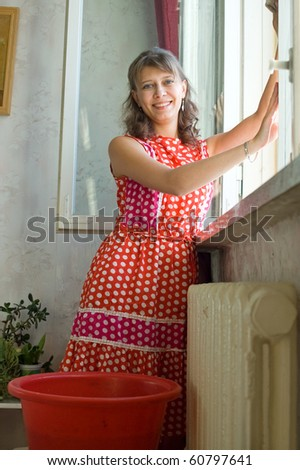 The woman washes a window in apartment - stock photo