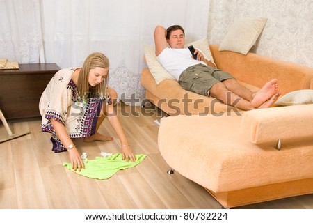 The woman washes the floors and my husband lying on the sofa - stock photo