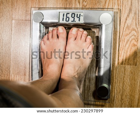 The woman weighed on the scales. Women's legs on the scales - stock photo