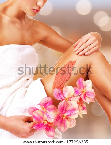 The woman with a beautiful body with flower using a scrub on her leg on a white background - stock photo