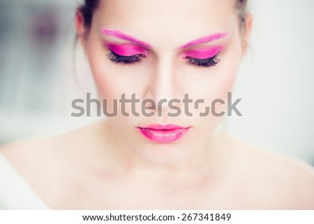 The woman with a bright pink make-up, pink eyebrows and false eyelashes. Studio portrait. - stock photo