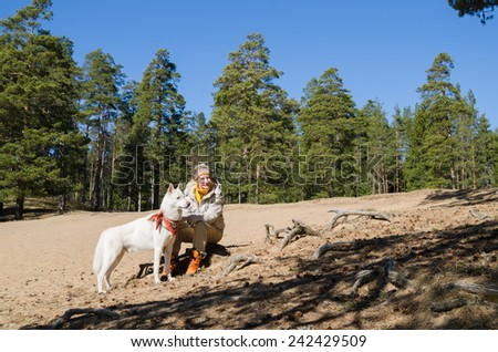 The woman with a white dog in a wood